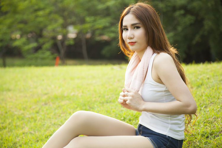 Woman Sitting On Field At Park