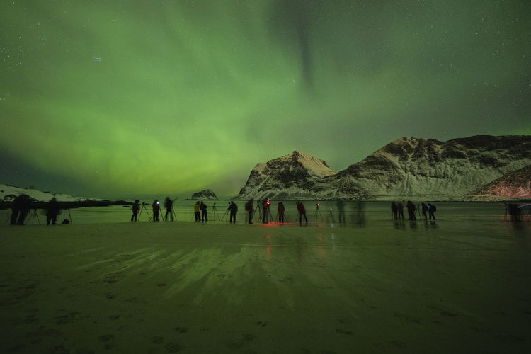 Group of people on land against sky at night