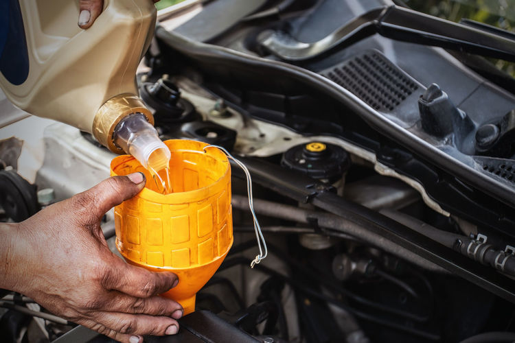 The car mechanic is adding oil to the engine, Automotive industry and garage concepts. Human Hand Hand Working Holding Real People Repairing Occupation Motor Vehicle Human Body Part Mode Of Transportation Car Engine Land Vehicle Transportation One Person Mechanic Technician Machinery Men Metal Finger Oil Refill Engine Oil Garage