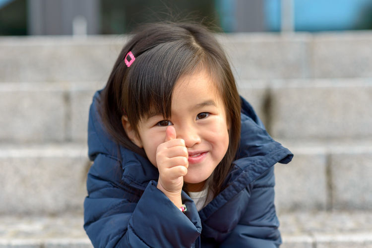 Close-up portrait of girl smiling while sitting on staircase