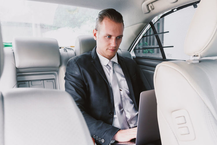 Young businessman using laptop while sitting in car
