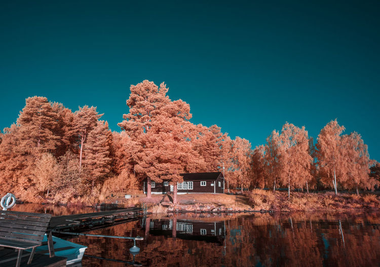 Infrared scenic view of lake against clear blue sky