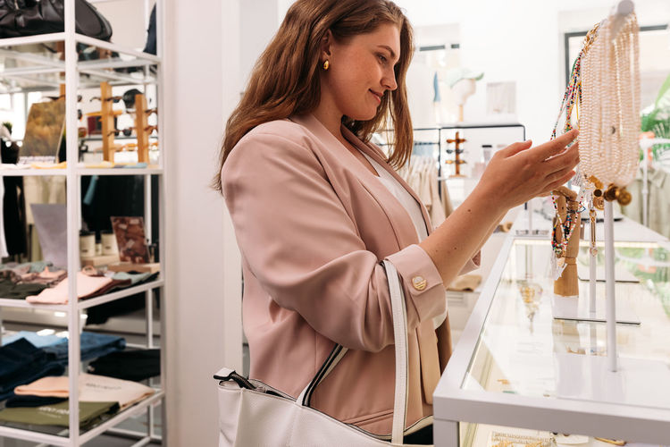 Side view of young woman holding camera in store