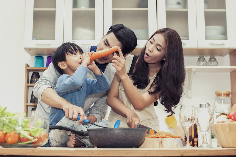 happy family Doing breakfast in the kitchen And the son is using carrots as a nose like Pinocchio Two People Togetherness Bonding Real People Lifestyles Casual Clothing Women Young Women Indoors  Food And Drink Emotion Child Young Adult Family Front View Smiling Happiness Adult Home Food Preparation