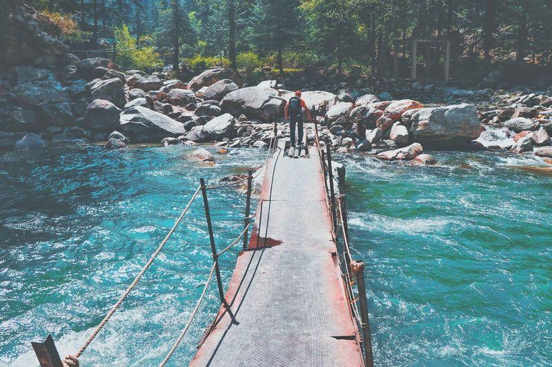 Man walking on footbridge over river