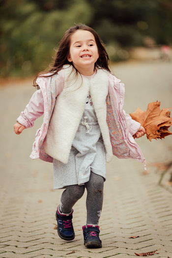 Full length of woman running on road while holding autumn leaves