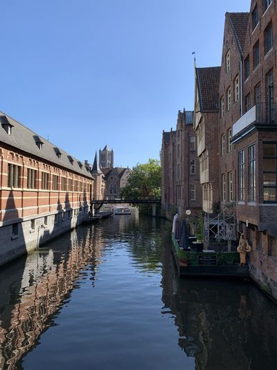 Bridge over canal by buildings against clear sky