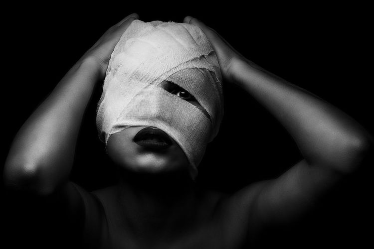 Close-Up Portrait Of Young Woman Face Wrapped In Bandage Against Black Background