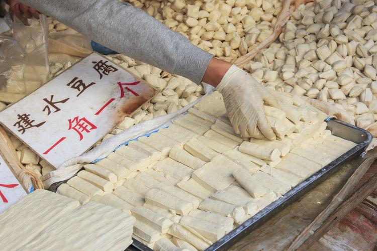Cropped Image Of Vendor Hand Arranging Tofu At Market Stall