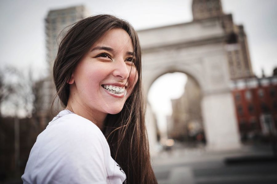 Smiling Happiness Toothy Smile One Person Portrait Cheerful Headshot Focus On Foreground Looking At Camera Long Hair Young Adult Outdoors Real People Built Structure Young Women Lifestyles Building Exterior City Day Architecture
