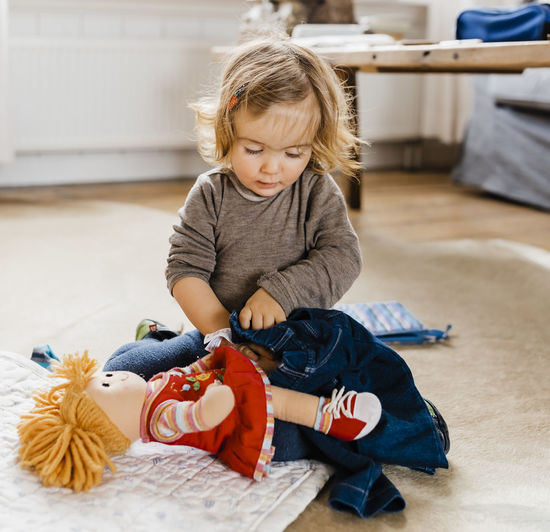 Cute Girl Playing With Doll At Home