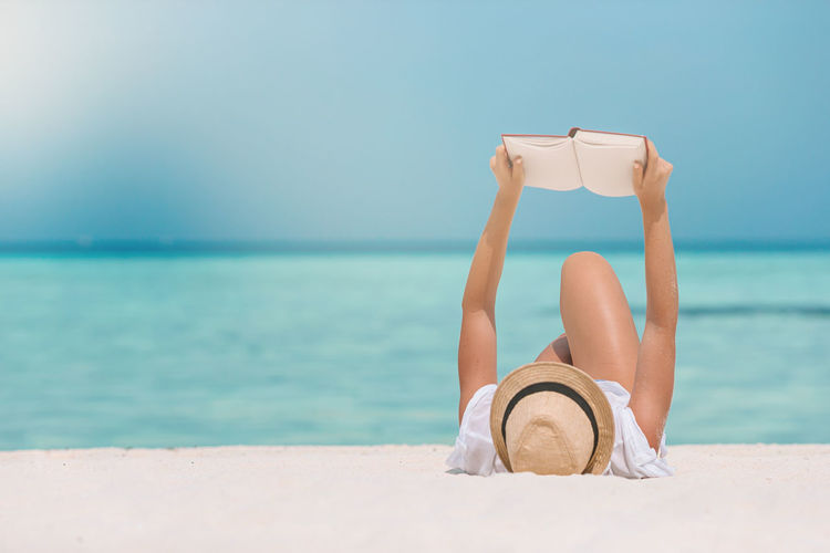 Man relaxing on beach against sky