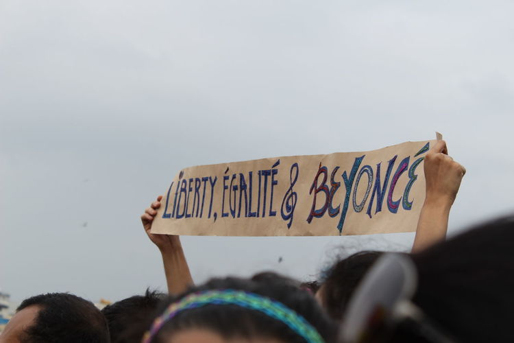 People holding banner against sky
