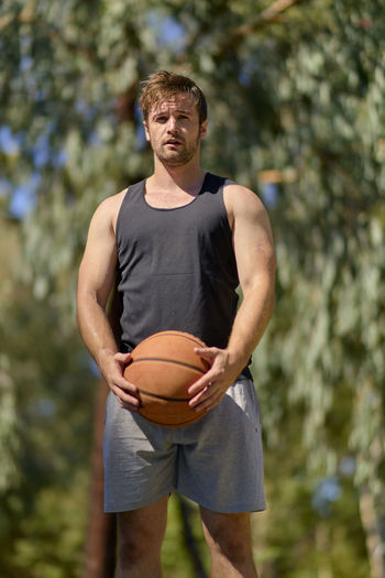 Basketball Adult Adults Only American Football - Ball Basketball - Sport Basketball Player Casual Clothing Day Focus On Foreground Front View Leisure Activity Men Mid Adult Mid Adult Men Nature One Person Outdoors People Playing Real People Sport Sportsman Standing Tree Young Adult
