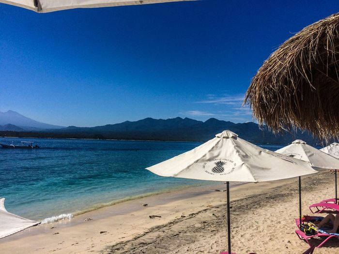 Beach Beauty In Nature Blue Clear Sky Day Landscape Leisure Activity Lifestyles Mountain Nature One Person Outdoors People Real People Sand Scenics Sea Sky Summer Sunlight Thatched Roof Tranquility Vacations Water