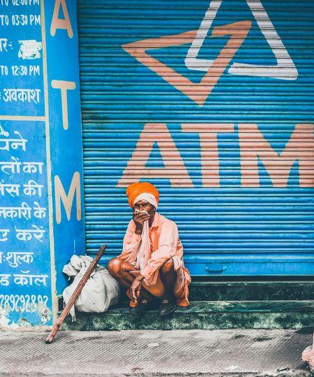 Man sitting against graffiti wall