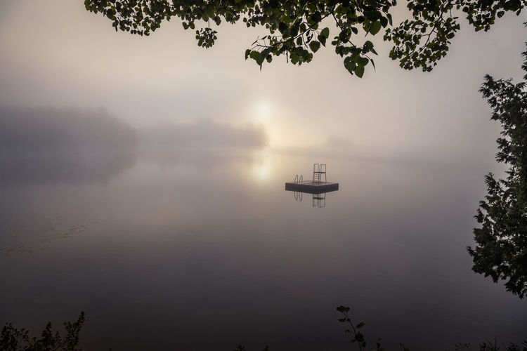 Scenic view of lake against sky during foggy weather