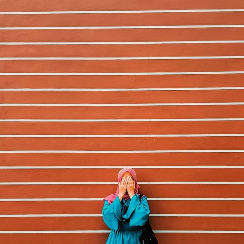 Woman covering face against wall