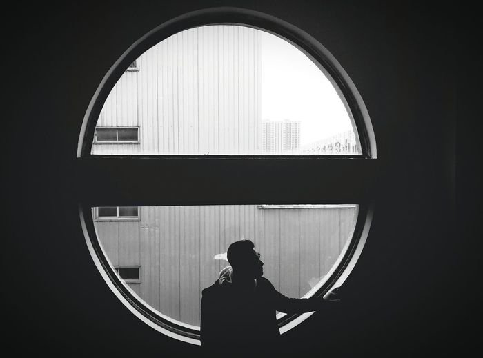High Angle View Of Man Standing Against Circular Glass Window In Darkroom