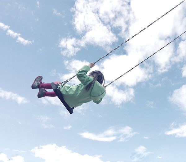 Low angle view of girl swinging on swing against cloudy sky