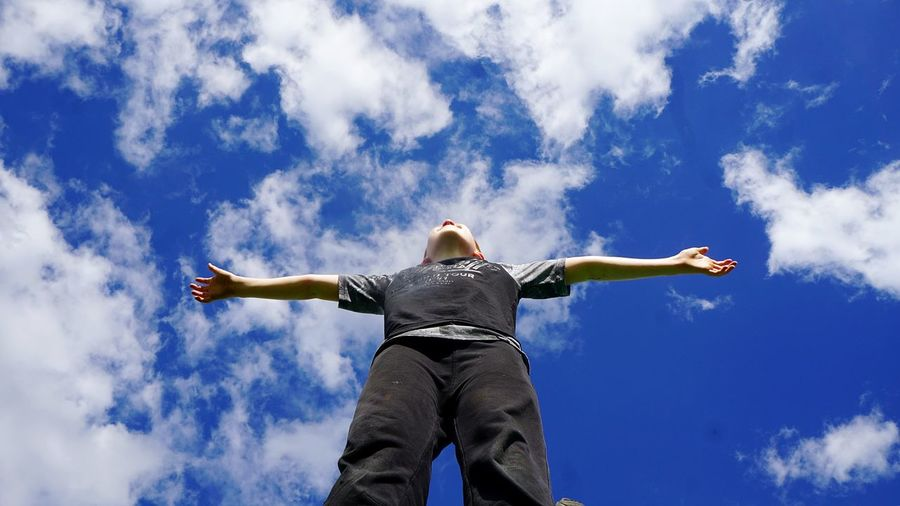 Low angle view of man standing with arms outstretched against blue sky
