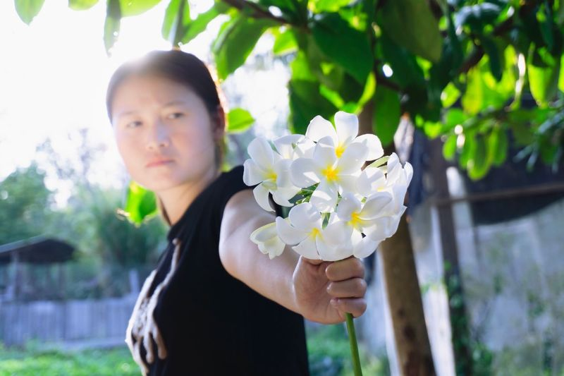 plumeria on hands. Beauty In Nature Sent  Flower Gift Plumeria One Person Plant Flowering Plant Flower Nature Portrait Fragility Lifestyles Real People Beauty In Nature Tree Hairstyle Freshness Day Focus On Foreground Waist Up Outdoors