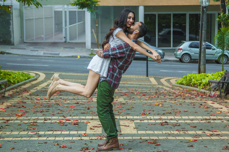 Man Lifting Girlfriend On Footpath In City