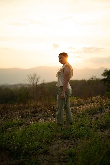 Full length of boy standing on field against sky during sunset
