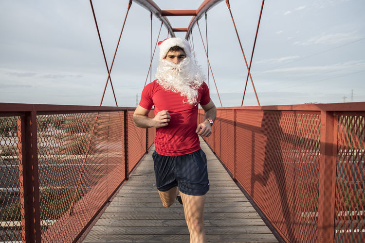 Christmas image of running Santa Claus Athlete Christmas Jogging Time Man Papa Noel Pedestrian Walkway Run Running Santa Claus Sportsman Adult Architecture Bridge Bridge - Man Made Structure Built Structure Cloud - Sky Day Fit Fitness Footbridge Front View Full Length Jogging Leisure Activity Lifestyles One Person Outdoors People Railing Real People Sky Sport Standing Training Young Adult Young Women