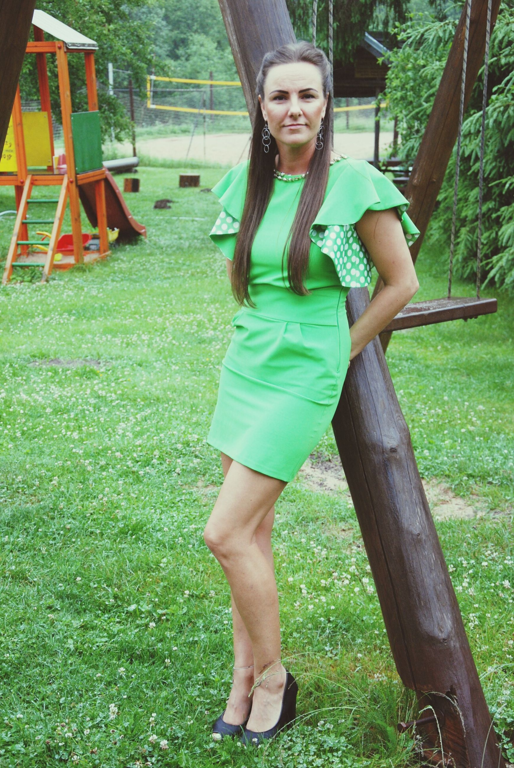 grass, one person, real people, leisure activity, casual clothing, day, green color, lifestyles, tree, full length, outdoors, young women, standing, beautiful woman, young adult, smiling, nature, happiness, looking at camera, portrait