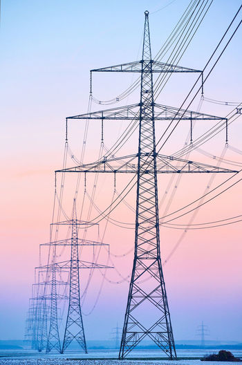 Electricity pylon by sea against clear sky