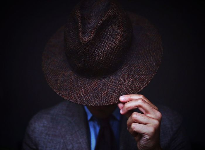Man wearing hat against black background