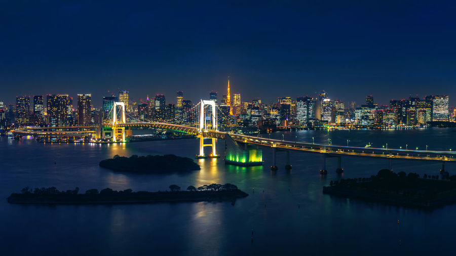 Panorama of tokyo cityscape and rainbow bridge at night. Built Structure Architecture City Building Exterior Night Bridge Illuminated Connection Water Sky Bridge - Man Made Structure Cityscape Transportation Building Travel Destinations Long Exposure Reflection Urban Skyline No People Office Building Exterior Skyscraper Outdoors