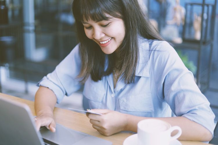 Smiling businesswoman doing online shopping over laptop in office