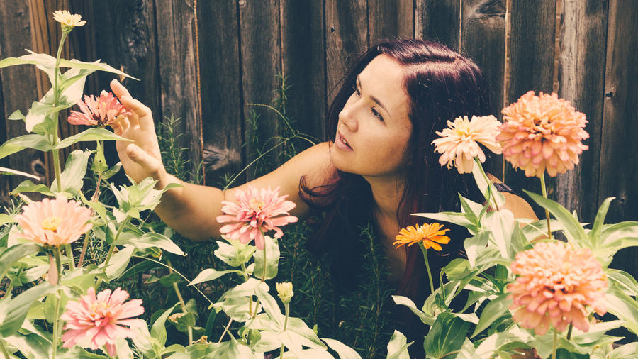 Close-Up Of Young Woman With Flowers And Plants