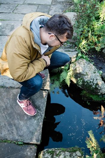 High angle view of man crouching on footpath by pond
