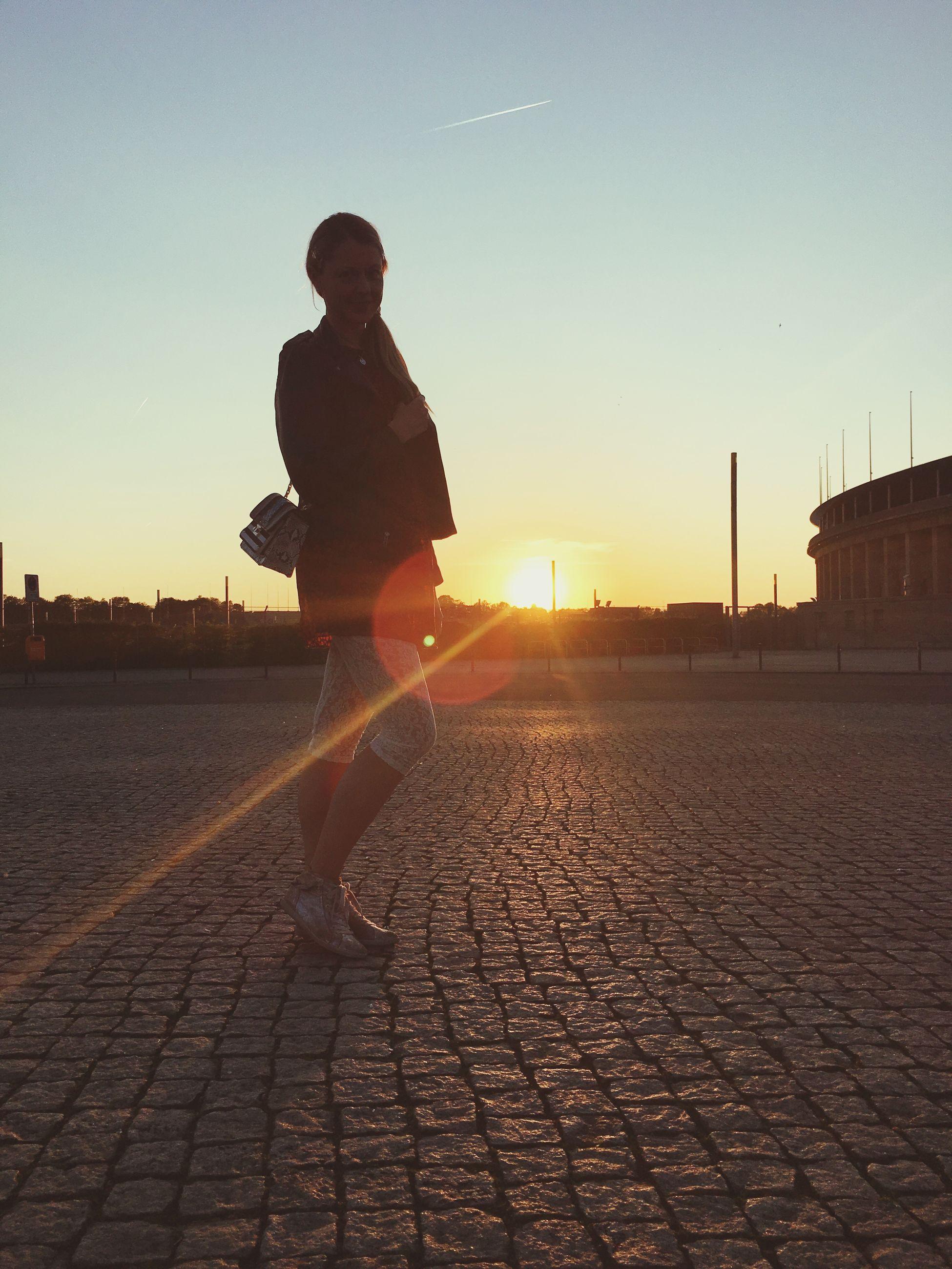 sun, sunset, sunbeam, lens flare, building exterior, sunlight, built structure, architecture, sky, statue, sculpture, human representation, city, street, silhouette, clear sky, outdoors, cobblestone, art, one person