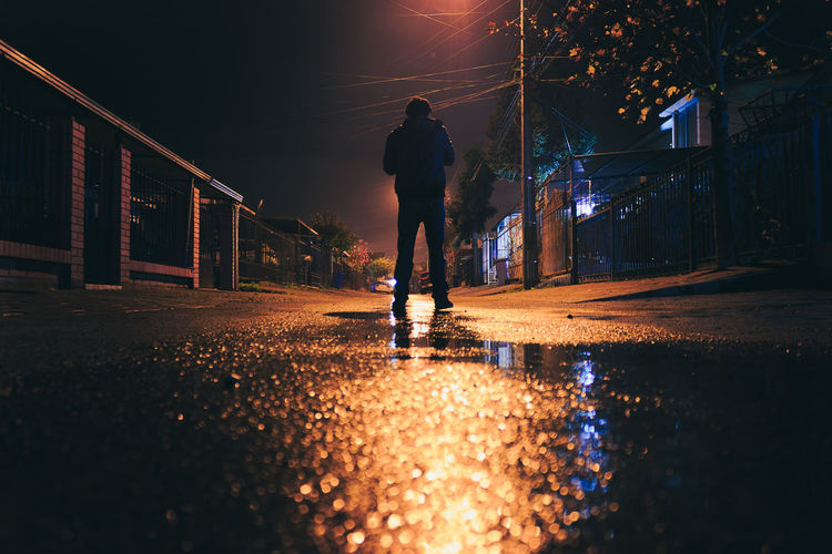 Man On Illuminated Street At Night