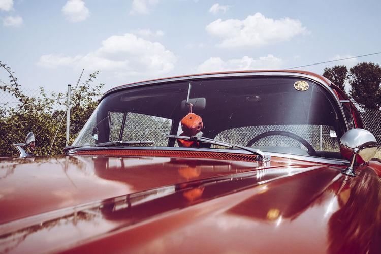 Close-Up Of Red Vintage Car Against Sky