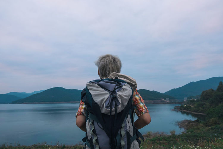 Rear view of backpacker standing at lakeshore against sky