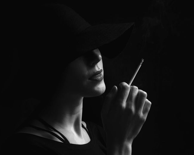 Close-up of woman holding cigarette against black background
