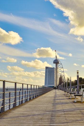 Pier over city against sky