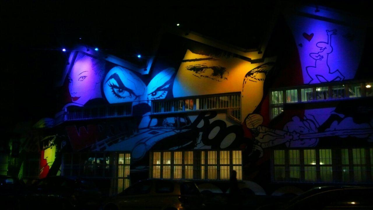 Graffiti On Illuminated Wall On Building At Night