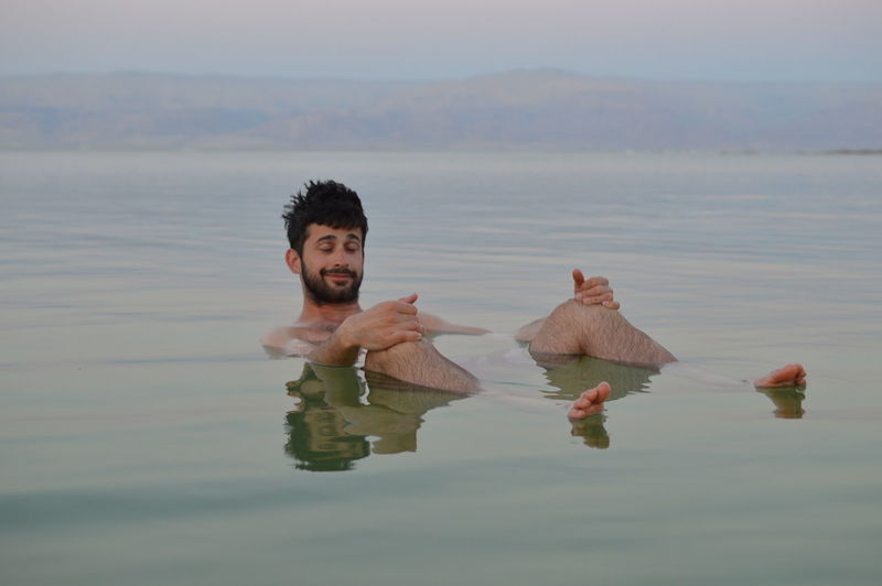 Young Man With Eyes Closed Relaxing In Dead Sea During Sunset
