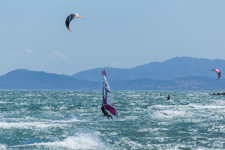 People kiteboarding and windsurfing against sky