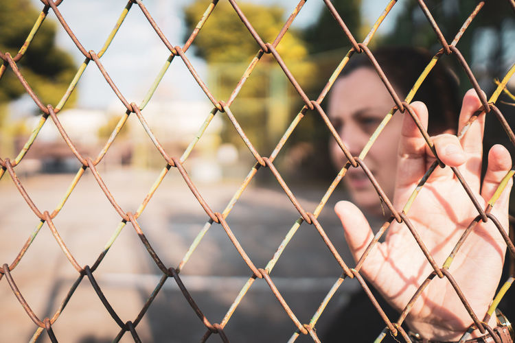 Close-up of hand seen through chainlink fence