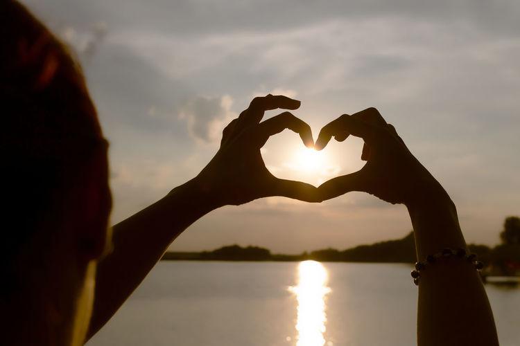 Sun shining over heart shape against sky during sunset