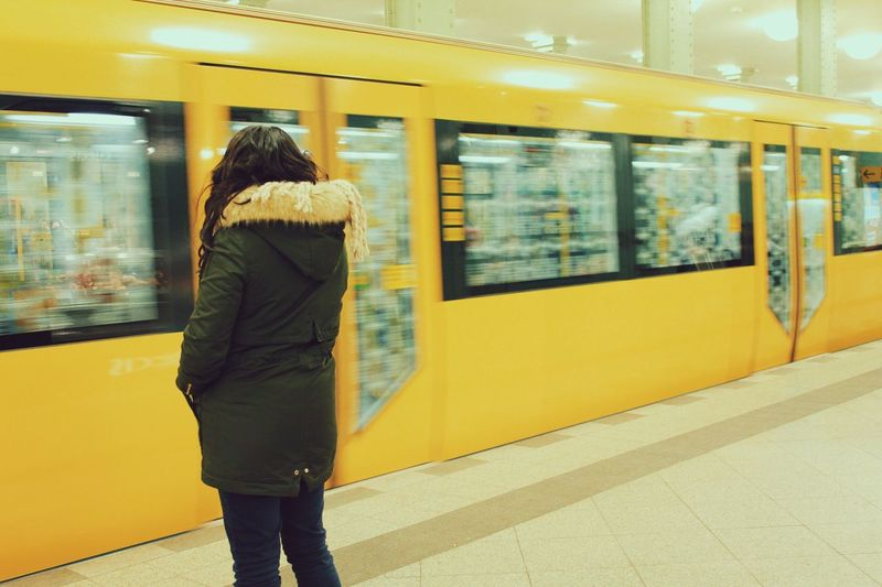 Rear View Of Woman Standing At Subway Station