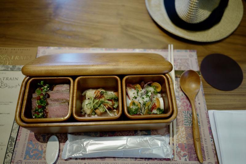 "OITA EAT ( NARISAWA BENTO ) : Thema ""cool off in the evening"" July, August menu / Kyushu Wagyu Steak Rice Bowl / Oita homebred chicken (Kanmuri jidori) , Japanese Tiger Prawn at Kumamoto, Bitter Melon and cucumber made Saga prefecture with Sesame dressing / horse mackerel (Sekiaji) and Seki grunt at Oita, Fukuoka potato and Kidney beans salad put Miyazaki hebesu (var. of citrus fruit from Miyazaki) dressing on a salad. / natural wood lunch box & Cutlery made in Oita prefecture LEICA Q 28mm F/2.8 Manual Mode Photography Oita JR KYUSHU SWEET TRAIN「或る列車」 Around The Kyushu NARISAWA NARISAWA BENTO Salad Food Freshness Close-up Cutlery High Angle View Japanese Food Lunch Box Ready-to-eat Still Life Table Tray Wood - Material"