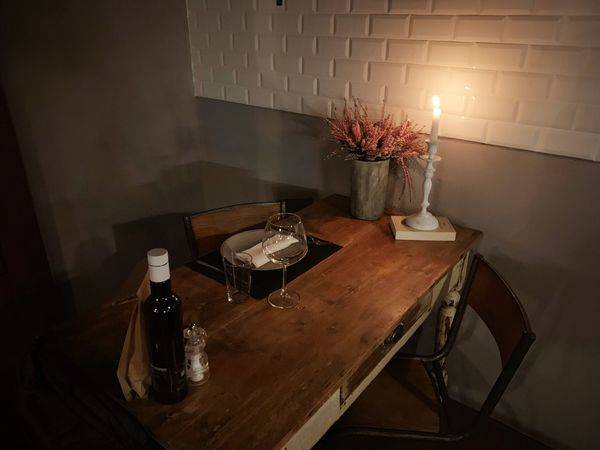 Dinner for one Indoors  Table Home Interior Wall - Building Feature No People Lighting Equipment Illuminated Domestic Room Home Furniture Bottle Candle Light - Natural Phenomenon Still Life Food And Drink